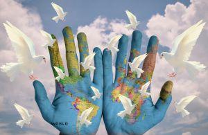handen met een wereldkaart erop en witte duiven